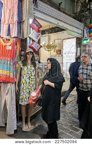 Tehran, Iran - April 29, 2017: A Woman In Black Islamic Clothes Stands Near A Full-length Female Man