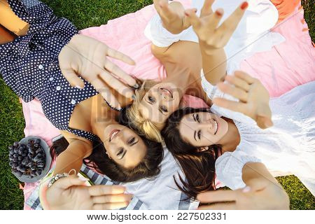 Group Of Young Attractive Women Having Fun In Park, Lying On The Grass