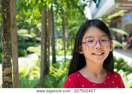 Cute Little Asian Chinese Girl With Glasses In Park Smiling
