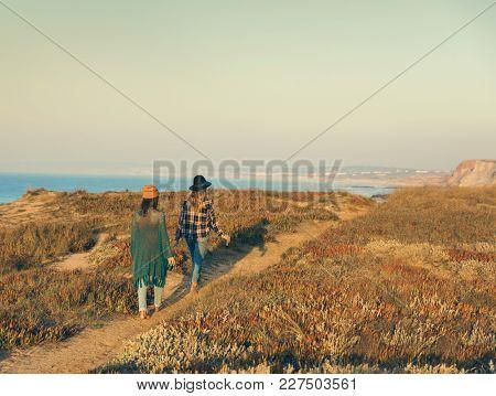 Two best friends walking on the coastline on a beautiful day