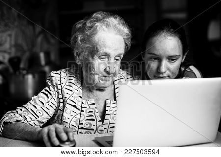 Teen girl teaches her grandmother to type on the laptop.