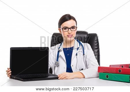 Portrait Of Young Attractive Female Doctor In White Coat Smiling Sitting At Her Workplace Looking In