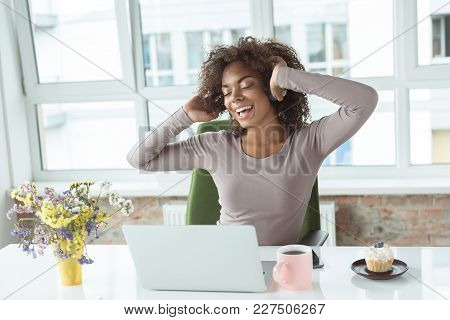 Portrait Of Cheerful Woman Listening Music While Locating At Desk In Room. She Having Job On Laptop