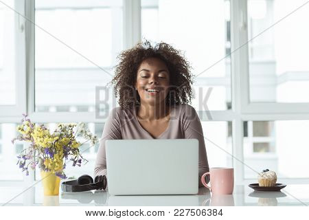 Portrait Of Outgoing Young Female Typing On Laptop While Sitting At Desk In Office