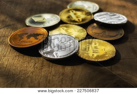 Family Of Cryptocurrency. Stack Of Shining Golden And Silver Coins With Sunlight On Wooden Backgroun