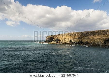 Rugged Coastline On Fuerteventura With Turquiose Water Against Partially Clouded Blue Sky