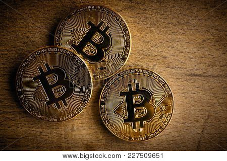 Three Virtual Shiny Coins (bitcoins) Heap On Dark Wooden Background. Close Up Of Real Physical Bitco