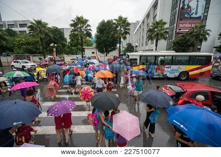 Hanoi, Vietnam - Aug 24, 2017: Busy Street With Crowded People Using Umbrella In Rainy Morning On A