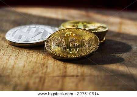 Stack Of Bitcoinsand Litecoin With A Single Coin Above. Photo Of Shining Bitcoins With Golden Sunray