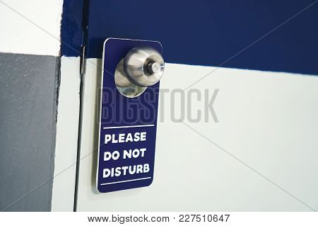 Label Please Do Not Disturb White With Blue Hang On The Door In Hotel.