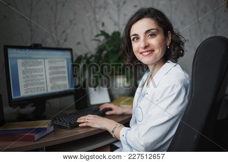 Smiling Woman Doctor In A White Medical Robe Sitting At A Table. On The Table Books, A Computer Moni