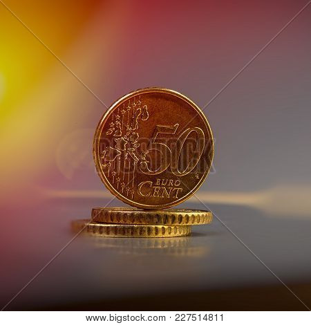 Coins Of Fifty Euro Cents Lie On A Pile Of Coins. Coins On The Blurred Background. Currency Of The E