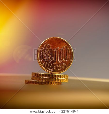 Coins Of Ten Euro Cents Lie On A Pile Of Coins. Coins On The Blurred Background. Currency Of The Eur