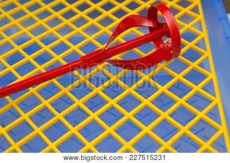 Repair, Redecorating Concept. A Concrete Or Paint Mixer On A Blue Plastic Pan With A Yellow Grid, Cl