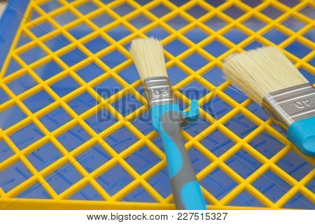 Repair, Redecorating Concept. Paint Brushes On A Blue Plastic Pan With A Yellow Grid, Close Up