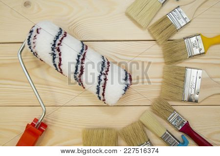 Repair, Redecorating Concept. A Set Of Wooden And Plastic New Paint Brushes And A Paint Roller On A