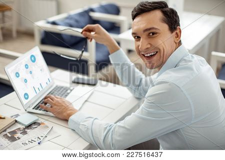 Good Job. Handsome Joyful Dark-haired Man Smiling And Working On His Laptop And Holding His Glasses
