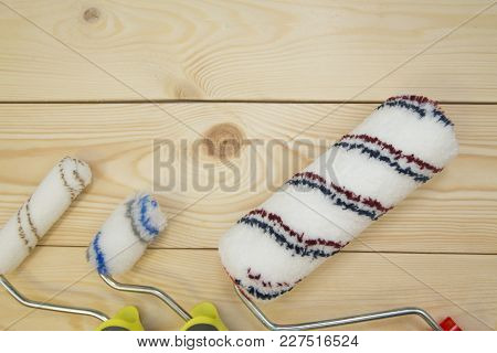 Repair, Redecorating Concept. A Set Of Paint Rollers On A Light Uncolored Wooden Background With Cop