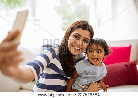 Smiling Indian Young Woman Taking Selfie With Her Little Daughter