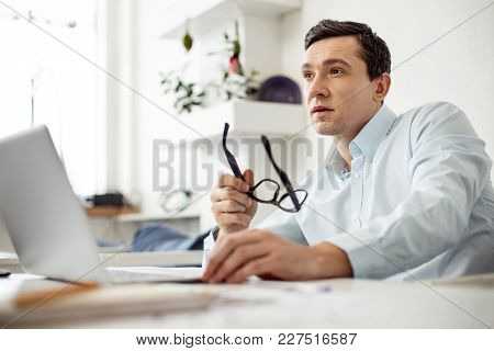 Thinking. Attractive Concentrated Dark-haired Man Working On His Laptop And Holding His Glasses Whil