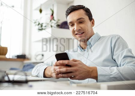In High Spirits. Attractive Alert Neat Dark-haired Man Smiling And Typing On His Phone While Sitting