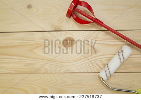 Repair, Redecorating Concept. A Paint Roller And A Concrete Mixer On A Light Uncolored Wooden Backgr