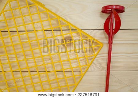 Repair, Redecorating Concept. A Yellow Plastic Grid And A Concrete Mixer On A Light Uncolored Wooden