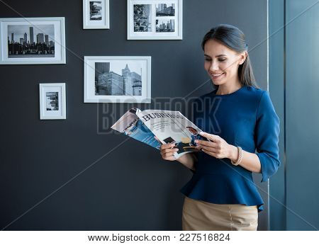 Joyful Working Time. Optimistic Stylish Young Woman Is Standing With Business Magazine And Reading W