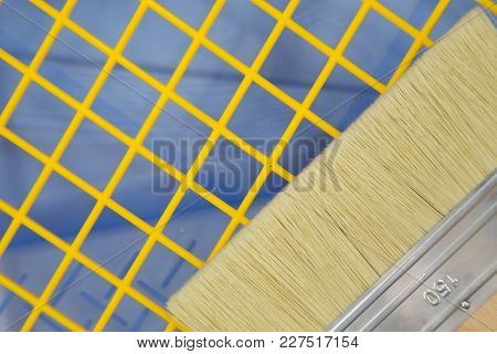 Repair, Redecorating Concept. A Wide Paint Brush On A Blue Plastic Pan With A Yellow Grid, Close Up,