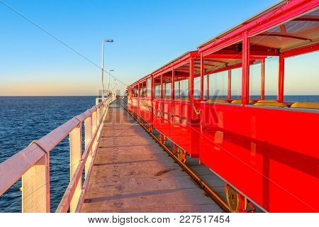 Perspective View Of Vintage Red Electric Train Going On Jetty Tracks In Busselton, Western Australia