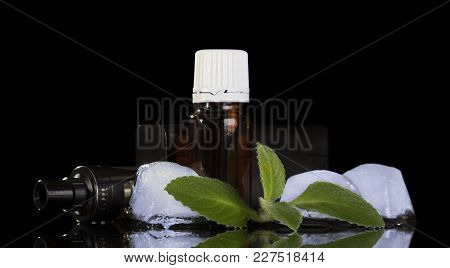 Electronic Cigarette, Liquid For Smoking, Ice Cubes And Mint Isolated On Black Background
