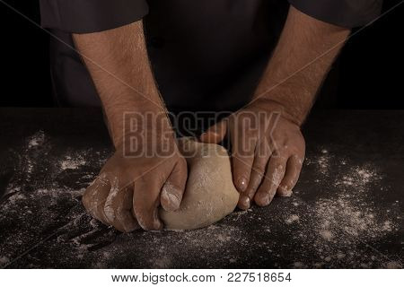 Baker's Hands Knead Dough For Bread, Isolated On Black