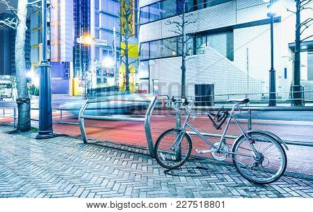 Night Scene With Parked Bicycle And Blurred Speeding Car In The City Center Of Tokyo Capital Of Japa