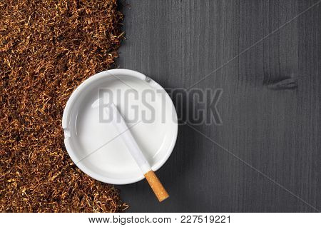 Ashtray, Cigarette And Tobacco On A Black Wooden Background, Top View With Space For Text