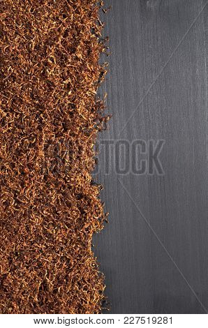 Cigarette Tobacco On A Black Wooden Background, Top View With Space For Text