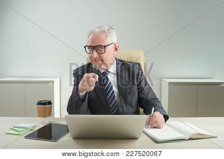 Senior Businessman In Glasses Conducting Job Interview