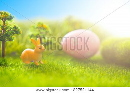 Rabbit And Easter Eggs In A Green Grass With Blue Sky.