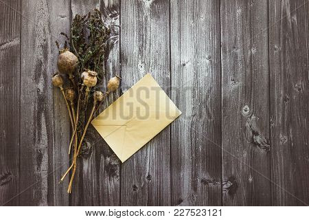 Dry Poppy Head In A Bouquet Of Dried Mint Lies On A Black Wooden Background And Beside It Lies An Em