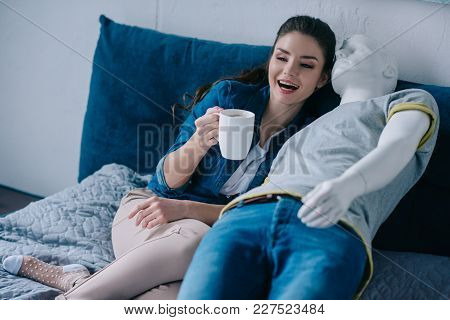 Young Woman With Cup Of Coffee Talking To Mannequin While Resting On Bed, Unrequited Love Concept