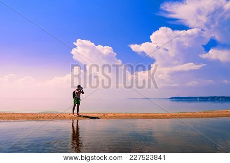Traveler Photographer A European With A Backpack Taking Pictures Of The Water In The Summer
