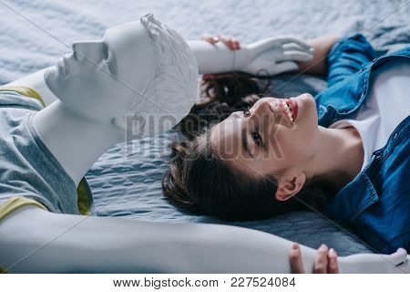 Side View Of Smiling Woman And Mannequin Lying On Bed, Loneliness Concept