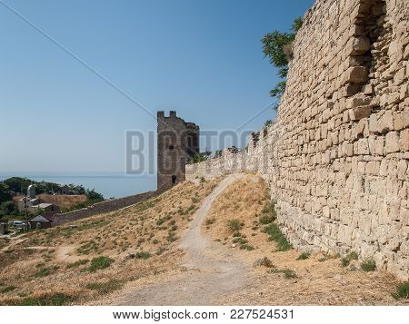 Stone Tower Of An Ancient Fortress With Adjoining Rocky Walls With Sea And Church Building On The Ba
