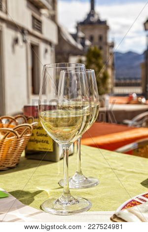 Holiday In Spain: Enjoying A Fresh Glass Of White Wine On The Terrace Of A Sidewalk Cafe In El Escor