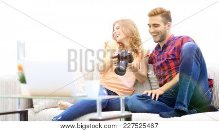 young couple with a photo camera makes viewing photos