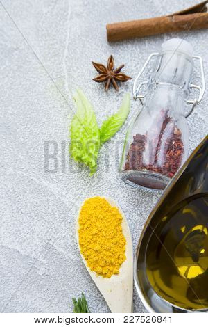 Dry Spices And Herbs In A Wooden Spoon And Glass Jar, Olive Oil And Cinnamon Stick On A Light Stone