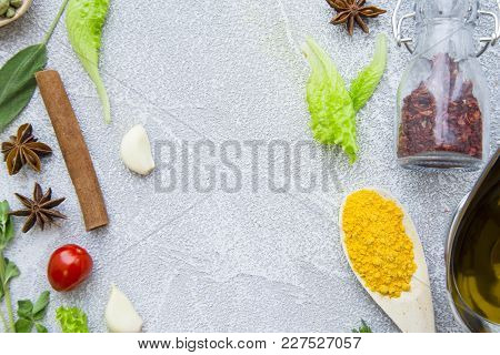 Dry Spices And Herbs In A Wooden Spoon And Glass Jar, Fresh Herbs Olive Oil And Cinnamon Stick On A