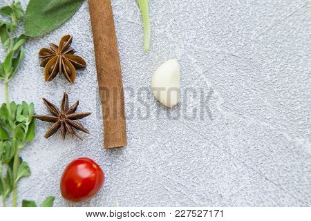 Fresh Herbs, Cherry Tomatoe And Cinnamon Stick On A Light Stone Background With Copy Space, Top View