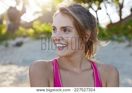 Close Up Shot Of Cheerful Female Model With Pleasant Smile, Dressed In Sport Clothing, Looks Away, H