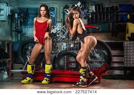 Two Sexy Young Female Models With Motorcycle In Garage