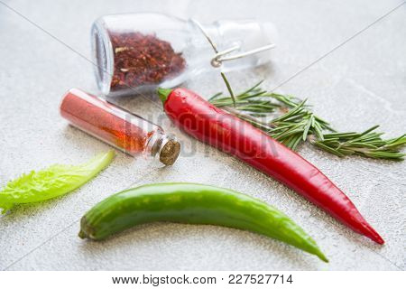 Dry Spices And Herbs In Glass Jars With Fresh Herb Springs And Chili Peppers On A Light Stone Backgr